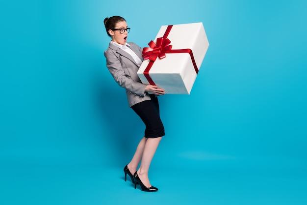 Foto in voller länge von erstauntem marketer-mädchen, das eine graue schwarze jacke trägt, die über blauem hintergrund isoliert ist