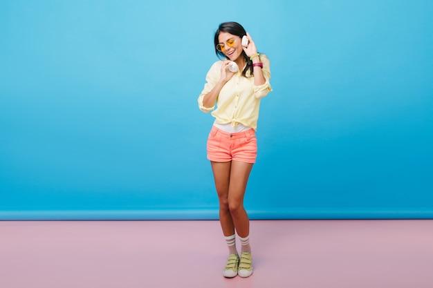 Foto in voller länge von formschön gebräuntem mädchen in rosa shorts, die mit vergnügen tanzen. fangen einer dunkelhaarigen europäischen frau in gelben schuhen, die musik in weißen kopfhörern hört.