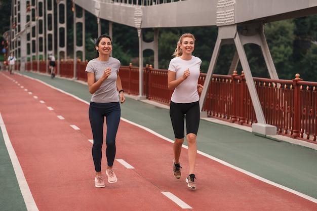 Foto in voller länge von glücklichen hübschen jungen damen in sportbekleidung, die am morgen in der stadt joggen