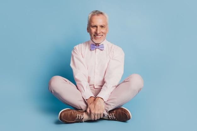 Foto in voller länge von gut gelauntem mann, der auf blauem hintergrund sitzt