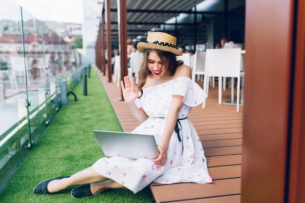 Foto in voller länge von hübschem mädchen mit langen haaren, die auf dem boden auf der terrasse sitzen. sie trägt ein weißes kleid mit nackten schultern, rotem lippenstift und hut. sie spricht auf einem laptop.