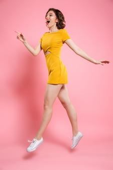 Foto in voller länge von hübschem mädchen mit rotem lippenmake-up, das mit finger zeigt, beiseite schauend, während über rosa springend