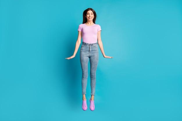 Foto in voller länge von hübschen jungen mädchen mit sprung-look-kamera tragen rosa t-shirt schuhe jeans isoliert blauer hintergrund