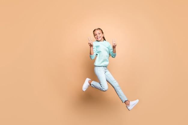 Foto in voller länge von hübscher schöner lustiger kleiner dame, die hoch oben springt und v-zeichen-symbole zeigt, die sich über das wochenende freuen, tragen blaue pulloverjeansschuhe isolierte beige farbwand