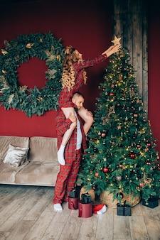 Foto in voller länge von kaukasischen mann und frau, die glücklich sind, ihren weihnachtsbaum zu hause zu schmücken