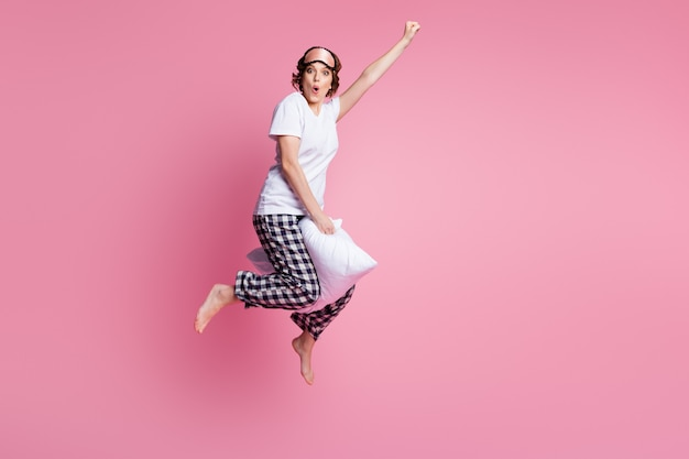 Foto in voller länge von lustigen verrückten dame springen hohes kissen zwischen beinen flug heben faust
