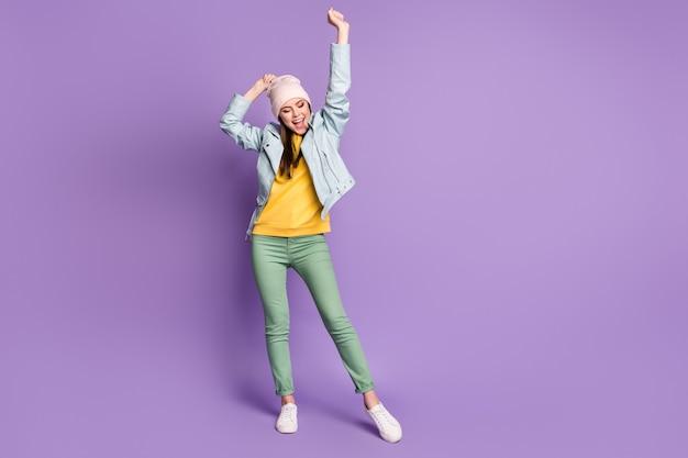 Foto in voller länge von lustiger attraktiver dame gute laune hebt die arme aufgeregt fröhlich tragen lässigen hut moderne blaue jacke grüne hose turnschuhe isoliert lila farbhintergrund