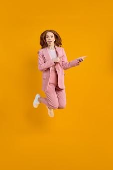 Foto in voller länge von lustiger kaukasischer dame in rosa anzug, die hoch springt, siehe niedrige einkaufspreise direkt ...