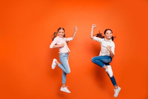 Foto in voller länge von positiven zwei blonden braunen haaren freundinnen mit langen schwänzen springen fäuste heben fühlen sich zufrieden tragen lässiges outfit über orange farbe hintergrund isoliert
