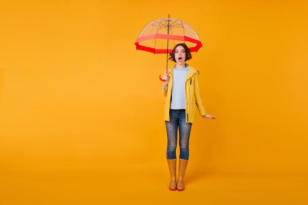 Foto in voller länge von schockiertem mädchen mit offenem mund stehend mit regenschirm. trendy junge dame in blue jeans posiert mit erstauntem gesichtsausdruck im studio.