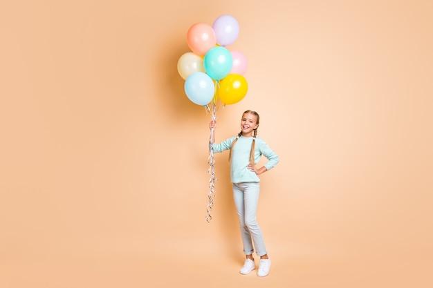 Foto in voller länge von schönen hübschen kleinen dame halten viele luftballons verträumte lustige lange zöpfe tragen blaue pullover jeans turnschuhe isoliert beige pastellfarbe wand