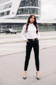 Foto in voller länge von stilvoller frau, gekleidet in schwarze hose und weißes hemd und stehend auf der straße gegen das moderne gebäude. stil und modekonzept