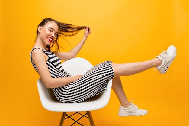 Foto in voller länge von stilvoller glücklicher frau mit roten lippen, passendem kleid und weißen turnschuhen, die im stuhl sitzen und mit ihren haaren über gelber wand spielen, platz für text