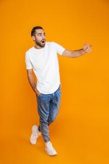 Foto in voller länge von überraschtem kerl 30s in t-shirt und jeans, die finger im stehen beiseite zeigen, isoliert