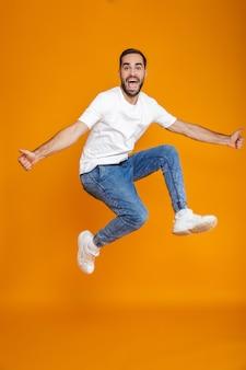 Foto in voller länge von unrasiertem kerl in t-shirt und jeans, die springen und spaß haben, isoliert