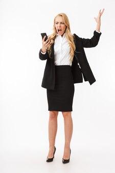 Foto in voller länge von unzufriedener geschäftsfrau, die büroanzug schreit, der auf smartphone schreit, lokalisiert