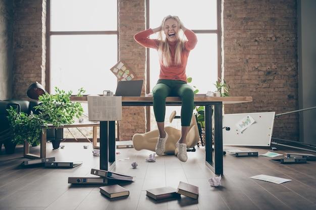Foto in voller länge von verrückten beschäftigten freiberuflichen sekretärin mit negativer stimmung gemacht fehler gefeuert sitzen auf dem tisch fühlen sich überarbeitet schreien schreien berühren blonde haare in chaotischen büroarbeitsplatz loft