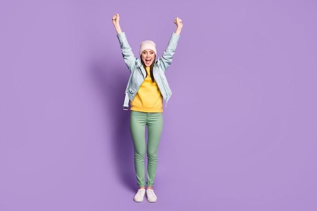 Foto in voller länge von verrückter attraktiver dame gute laune hebt die arme aufgeregt funky fröhlich tragen lässigen hut moderne blaue jacke grüne hosen schuhe isoliert lila farbhintergrund
