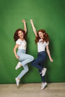 Foto in voller länge von zwei freudigen mädchen 20s mit ingwerhaar in lässigen jeans lächelnd und springend mit erhobenen armen, lokalisiert über grünem hintergrund