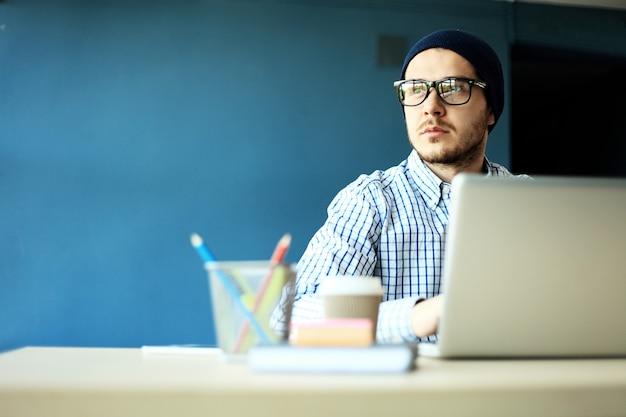 Foto junger und talentfinanzmanager, der mit neuem projekt arbeitet. hübscher mann, der von seinem hauptbüro arbeitet. analysieren sie geschäftspläne auf einem laptop.