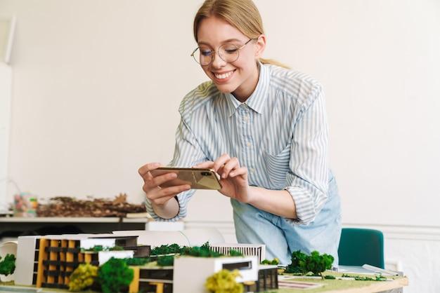 Foto lächelnde architektin, die ein foto auf dem handy macht, während sie einen entwurf mit einem hausmodell am arbeitsplatz entwirft