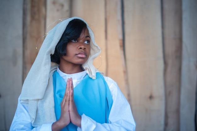 Foto mit kopienraum einer schwarzen jungfrau maria-darstellung, die in einer krippe betet