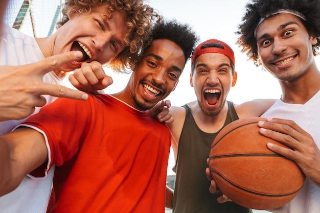 Foto nahaufnahme der amerikanischen sportlichen männer lächelnd und selfie nehmend, während basketball am spielplatz im freien während des sonnigen sommertages spielen