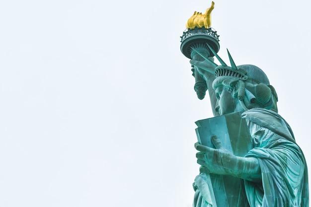 Foto nahaufnahme der freiheitsstatue an einem sonnigen tag und blauem himmel mit wolken. freiheitsinsel. nyc, usa.