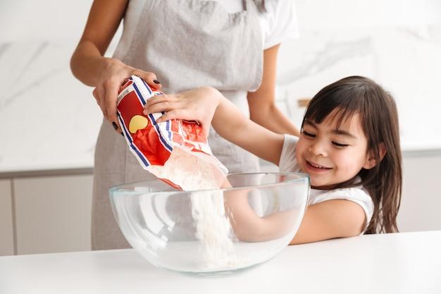 Foto nahaufnahme der hausfrau in der schürze mit ihrer kleinen tochter, die zusammen kocht, gebäck mit mehl in der küche zu hause backend