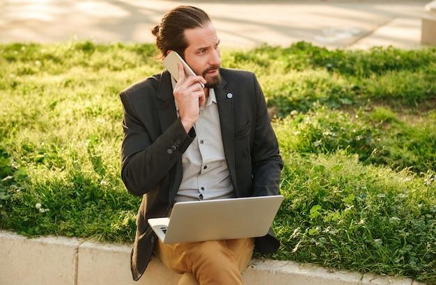 Foto-nahaufnahme des kaukasischen geschäftsmannes mit gebundenem haar, das auf silbernem laptop arbeitet und auf handy spricht, während im grünen park während des sonnigen tages sitzt