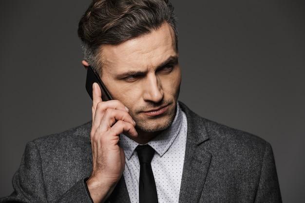 Foto-nahaufnahme des konzentrierten mannes 30s gekleidet in sachlichem kostüm mit krawatte, die beiseite schaut, während auf handy spricht, lokalisiert über graue wand