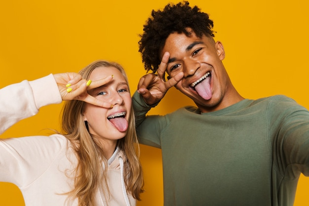 Foto nahaufnahme eines schönen paares mann und frau 16-18, die spaß haben und selfie machen, isoliert auf gelbem hintergrund