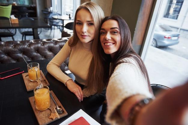 Foto vom telefon des mädchens. junge freundinnen machen selfie im restaurant mit zwei gelben getränken auf dem tisch