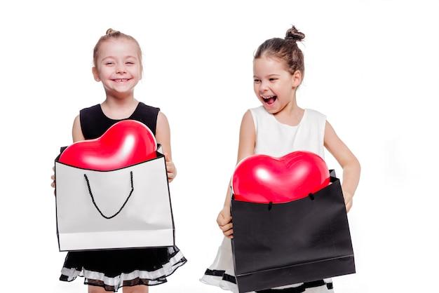 Foto von 2 kleinen mädchen mit eleganten kleidern halten große taschen mit herzförmigen luftballons im inneren
