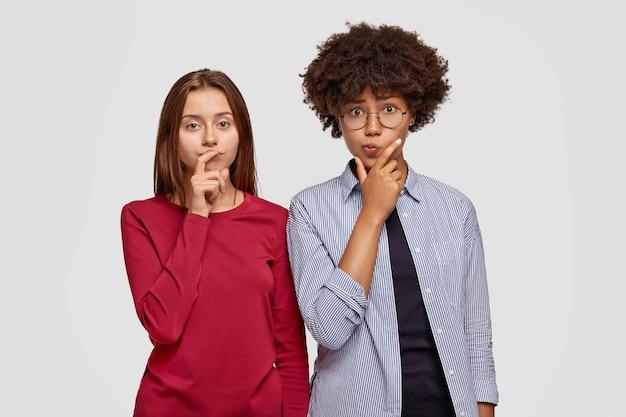 Foto von ahnungslosen zwei freundinnen verschiedener rasse