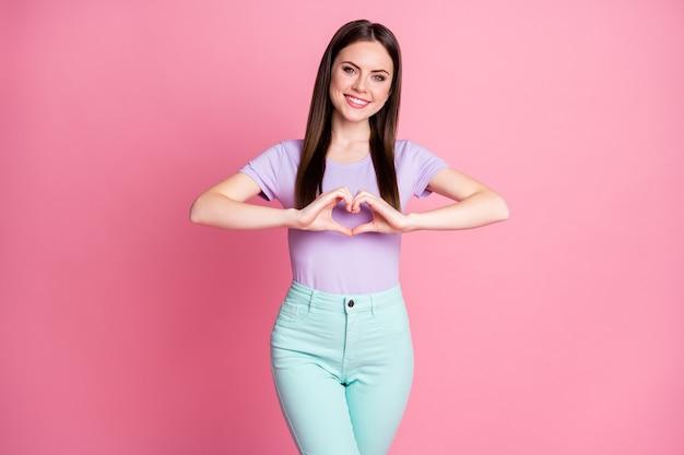 Foto von attraktiven, erstaunlichen, schönen damenshows machen arme herzform figur romantische stimmung einladender freund date abschlussball tragen lässige violette t-shirt-hose isoliert rosa pastellfarbener hintergrund