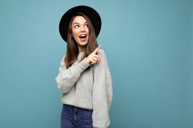 Foto von attraktiver brünette glücklich schockiert fröhliche junge frau, die mit dem finger auf freien platz für text zeigt, der graues trikot und schwarzen hut einzeln auf blauem hintergrund trägt.