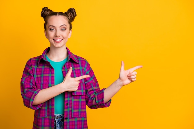 Foto von attraktiver charmanter positiver teenie-dame zwei lustige brötchen gute laune direkte finger leeren raum neuheit produkt tragen lässig kariertes magenta-shirt isoliert gelb heller farbhintergrund
