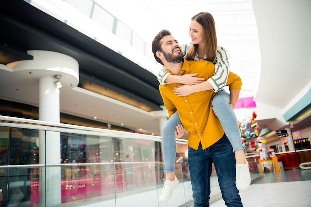 Foto von attraktiver dame, gutaussehender mann, paar besucht einkaufszentrum zusammen zu fuß huckepack tragen pose spaß beim spielen tragen lässiges jeanshemd outfit drinnen