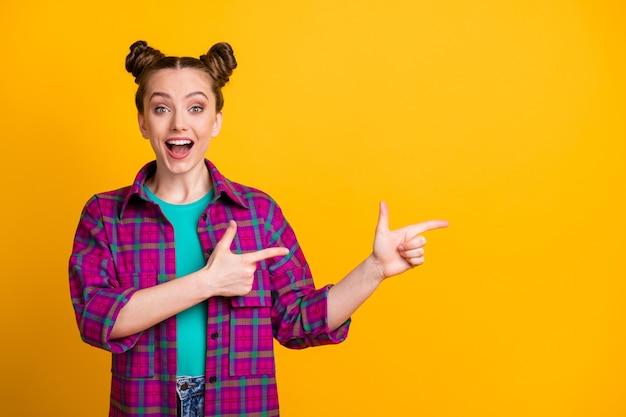 Foto von attraktiver fröhlicher aufgeregter teenager-dame zwei lustige brötchen gute laune direkte finger leeren raum zeigen neuheit tragen lässig kariertes magentafarbenes hemd isoliert gelber heller farbhintergrund