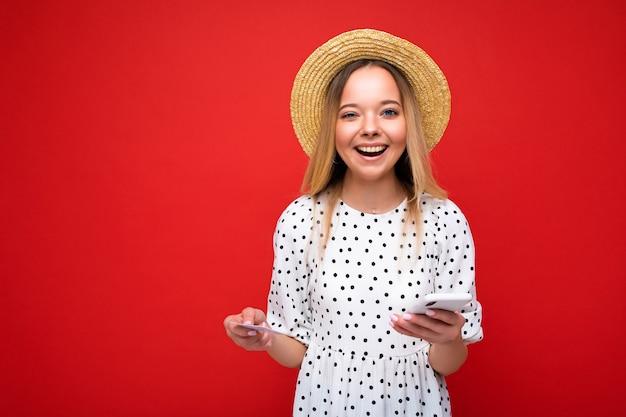 Foto von attraktiver positiver blonder frau in sommerkleidung, die handy benutzt und kreditkarte hält