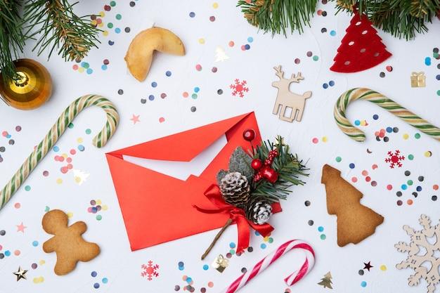 Foto von brief, weihnachtstanne, süßigkeiten, kekse auf weißem tisch
