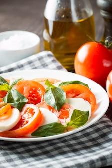 Foto von caprese-salat mit tomaten, basilikum, mozzarella, oliven und olivenöl auf hölzernem hintergrund. italienische traditionelle caprese salatbestandteile. mediterranes, biologisches und natürliches lebensmittelkonzept.