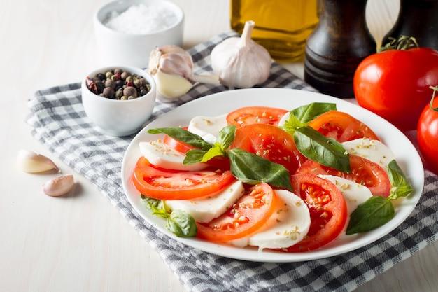 Foto von caprese-salat mit tomaten, basilikum, mozzarella, oliven und olivenöl. italienische traditionelle caprese salatbestandteile. mediterranes, biologisches und natürliches lebensmittelkonzept.