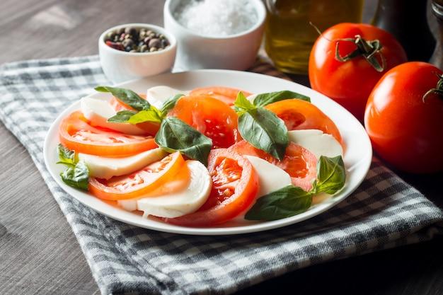 Foto von caprese-salat mit tomaten, basilikum, mozzarella, oliven und olivenöl