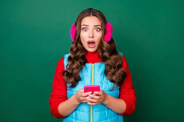 Foto von charmanter süßer verärgerter junger dame mit offenem mund halten telefon schlechte nachrichten lesen lieblingsgeschäft geschlossen tragen rosa ohrwärmer blaue weste mit reißverschluss roter pullover isoliert grüner hintergrund