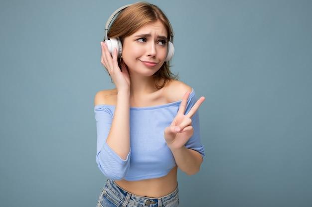 Foto von charmanter trauriger verärgerter junger blonder frau mit blauem bauchfreiem oberteil isoliert auf blauem hintergrund