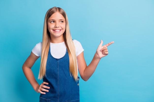 Foto von coolen optimistischen teenager blonden langen mädchen point look leeren raum tragen weißes t-shirt jeanskleid isoliert auf blauem hintergrund