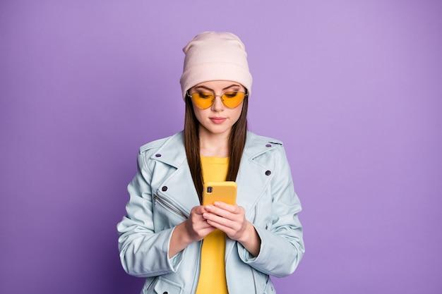 Foto von coolen, stilvollen hübschen damenstraßenkleidung halten telefonhände lesen freunde chatten nachrichten tragen sonnenspezifikationen freizeithut blaue moderne jacke isoliert lila farbhintergrund