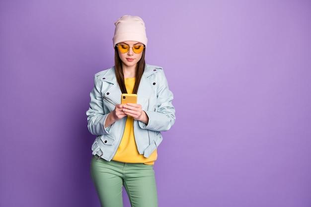 Foto von coolen, stylischen hübschen lady street look-kleidung halten telefonfreunde, die nachrichten chatten, tragen sonnenspezifikationen lässiger hut blaue moderne jacke pulloverhose isoliert lila farbhintergrund